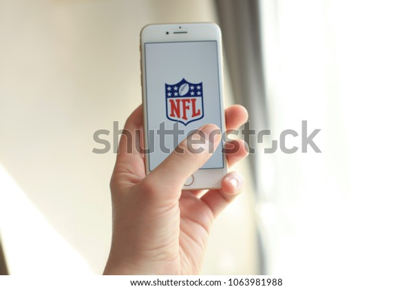 """MINSK, BELARUS – April 07, 2018: Woman holding brand new white Apple iPhone 7. The logo of the brand """"NFL National Football League""""."""