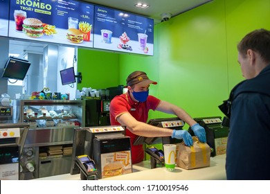 MINSK, BELARUS - April 20, 2020: Worker in protective mask issues an order to client at McDonald's restaurant. Lifestyle during Coronavirus epidemic.