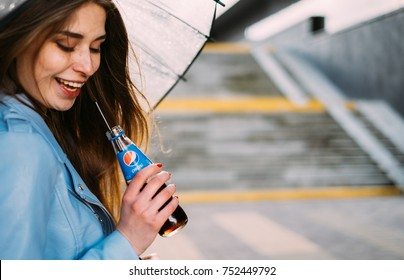 MINSK, BELARUS - APRIL, 2017: Happy woman with ubrella drinking pepsi