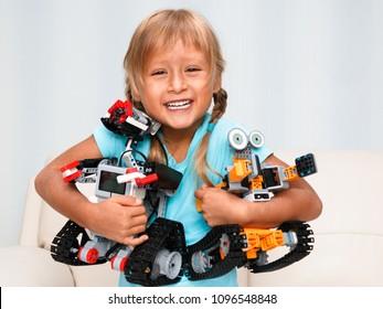 Minsk, Belarus - April, 2018. A little girl is playing with Jimu Robot Ubtech and Lego Mindstorms EV3. STEM education. Code the bot. Robotics.
