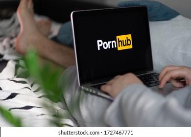 MINSK, BELARUS - April 2020: Apple laptop Macbook Pro with PornHub logo on display monitor, man's hands on keyboard.