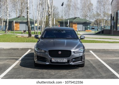 MINSK, BELARUS - APRIL 21, 2018: Jaguar XE parked in front of birch trees. Jaguar XE combines perfectly-proportioned sports saloon styling, advanced driving dynamics, efficiency and performance.