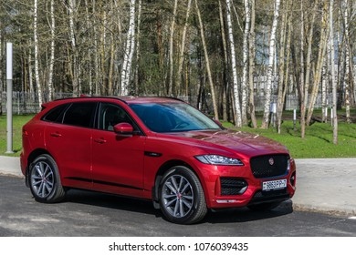 Minsk, Belarus - April 22, 2018: Bright red performance SUV Jaguar F-Pace stopped on the parking. Trees in the background.