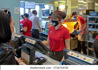 MINSK, BELARUS - April 27, 2020: Workers in medical masks serve customers at McDonald's restaurant during a Coronavirus epidemic. Lifestyle during pandemic.