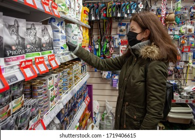 MINSK, BELARUS - April 27, 2020: Buyer wearing a protective mask. Shopping during the pandemic. Man shopping pet food in pet shop.