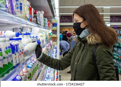 MINSK, BELARUS - April 27, 2020: Woman in a protective mask and gloves holding milk bottle in grocery store during coronavirus epidemic. Man checks product expiration date before buying it.