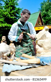 MINSK, BELARUS - APRIL 30: Festival of ethnic arts.  An unidentified young male hackers wooden bear at the festival of ethnic arts in Minsk, Belarus. on April 30, 2009.