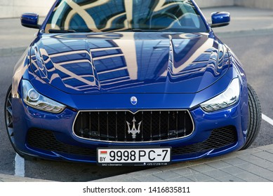 Minsk, Belarus - Aug 2018. Maserati Ghibli - blue lexury sport sedan parked at street. Maserati Trident Logo - Luxury Car Manufacturer Based in Italy.