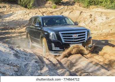 MINSK, BELARUS - AUGUST 1, 2017: Cadillac Escalade drives off road in a deep sand quarry. Cadillac Escalade is a luxury SUV and a first light truck in the history of the Cadillac brand.