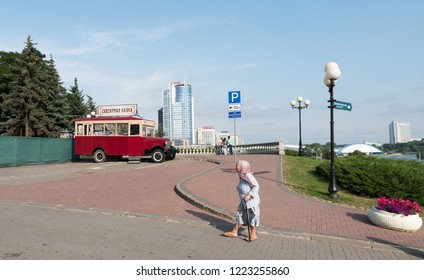Minsk, Belarus August 12, 2017: Eldery church goer passing by souvenir shop on Svobody Square