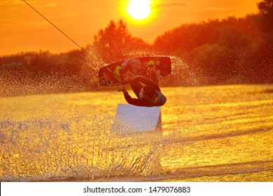 Minsk, Belarus - august 12.08.2019 Wakeboarder making tricks. Low angle shot of man wakeboarding on a lake. Man water skiing at sunset.