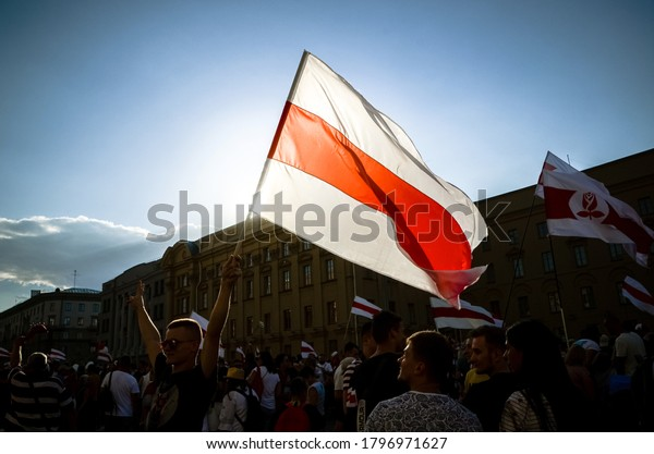 Minsk, Belarus - August 16, 2020: Belarusian people participate in peaceful protest after presidential elections in Belarus. Person holds historical flag of Belarus