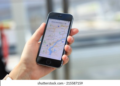 MINSK, BELARUS - AUGUST 17, 2014: Woman holding on Google Maps application on new black Apple iPhone 5S. Google Maps is most popular mapping service for mobile provided by Google.