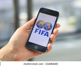 MINSK, BELARUS - AUGUST 17, 2014: Woman holding brand new black Apple iPhone 5S. The official logo of the brand Federation Internationale de Football Associations, FIFA.