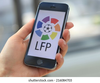 MINSK, BELARUS - AUGUST 17, 2014: Woman holding brand new black Apple iPhone 5S. The official logo of the Spanish championship in football, La Liga. Liga de Futbol Profesional, LFP