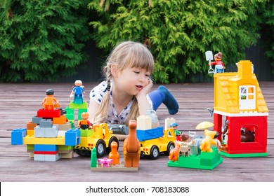 Minsk, Belarus - August, 2017. A little girl is an elementary school student lying on a wooden floor in the garden and playing Lego Duplo toys. Modern training. A game.