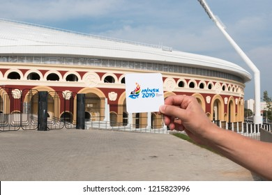 Minsk, Belarus. August, 2018. Man holds the logo of the second European games to be held in the city of Minsk in June 2019. In the background are the city's stadiums where events will take place.