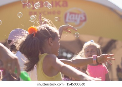 Minsk, Belarus, August 24, 2019. children catch soap bubbles in a summer park on holiday