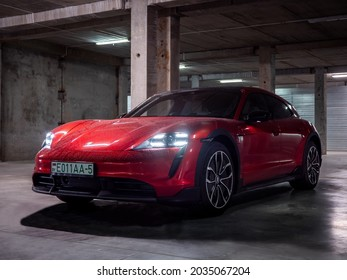 Minsk, Belarus - August 25, 2021: Porsche Taycan Sport Turismo in the underground parking. The car is covered with raindrops. This model is a more practical alternative to the Taycan electric car.
