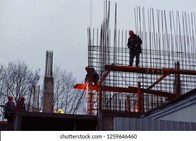 Minsk, Belarus - Dec 2018. Worker knitting metal rods bars into framework reinforcement for concrete pouring at construction site. Group of workers in safety uniform install reinforced colum at night