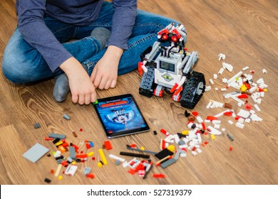 Minsk, Belarus - December 1, 2016: Teenager schoolboy sitting on the floor and controls the robot  Walle with iPad. Lego EV 3. School Robotics. Modern training. The hottest gadgets. E-learning.