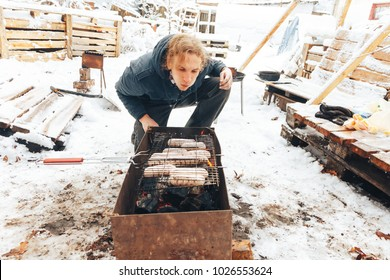 Minsk, Belarus, December 10, 2017 Volunteer's Day A man is cooking a barbecue of sausages