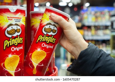 MINSK, BELARUS - December 19, 2019: A buyer buys Pringles chips at a supermarket. Hand hold a new tube of Pringles Potato Chips.