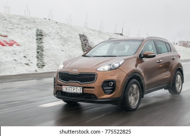 MINSK, BELARUS - DECEMBER 20, 2017: Brown Kia Sportage drive on a road during nasty winter weather. Snow and rain fall down. Dirty wet road.