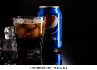 MINSK, BELARUS - DECEMBER 20, 2017: Can of Pepsi cola with glass of pepsi with ice over black background, Pepsi is a carbonated soft drink produced PepsiCo. Created in 1893