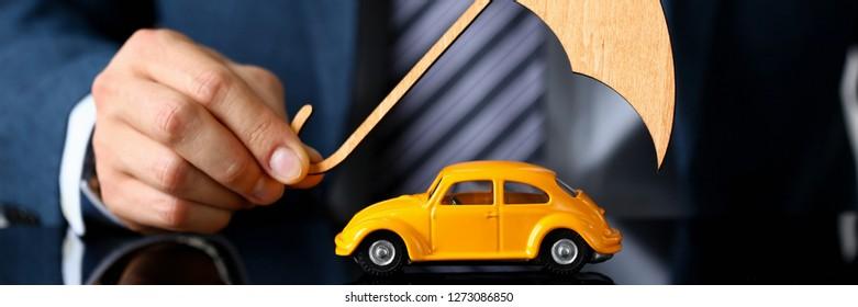 Minsk, Belarus - december 20, 2018 : Man holding wood umbrella above model Volkswagen car beetle in hand Illustrative editorial