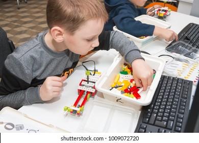 Minsk, Belarus. December, 2017. Teenager boy constructs and programmes Lego Robot WeDo at elementary STEM school. Stem education. Competition.
