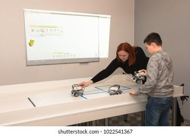 Minsk, Belarus. December, 2017. Teenager boy and a teacher construct and programme Lego Robot Mindstorms EV3 at robotics school. Education of children and teenagers. Stem education.