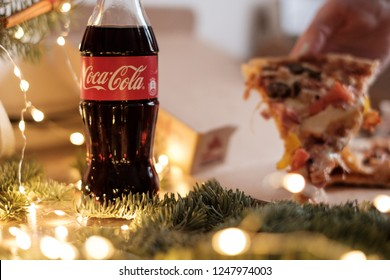 MINSK, BELARUS - DECEMBER, 2018: Bottle with coca cola at christmas background and female hand holding slice of pizza