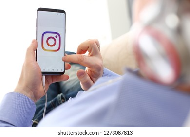 Minsk, Belarus - December 25, 2018: Male arm hold samsung galaxy s9 phone with instagram social network web application logo on display closeup while lying on couch at home wearing headphones