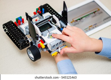Minsk, Belarus - December 29, 2016: Teenager schoolboy sitting on the table and controls the robot  Car with iPad. Lego EV 3. Mindstorms. School Robotics. Modern training. The hottest gadgets.