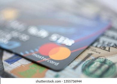 Minsk, Belarus - February 08,2017: Embossed chipped mastercard credit card and hundred dollar bank notes closeup