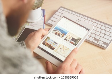 MINSK, BELARUS, FEBRUARY 10, 2018: The man's hands with tablet searching and booking an appartments on Airbnb website. The white keyboard and the succulent plant on the wooden table background.