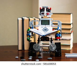 Minsk, Belarus -  February 11, 2017: Lego robot reading a book. Pile of books in the background. Robot in the library.  School. E-learning.  STEM education.