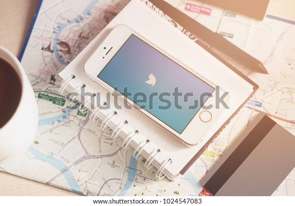 MINSK, BELARUS, FEBRUARY 11, 2018: Apple smartphone (Iphone) was started the Twitter app. The white book and the pen on the map and table background. Credit card and cup of coffee.