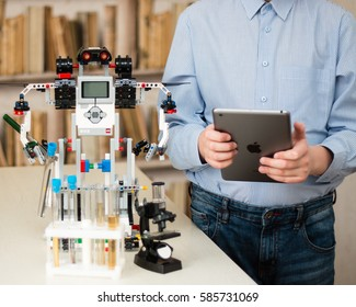 Minsk, Belarus -  February 14, 2017:  Lego Rodot and teenager conduct experiments in chemistry and do some tests. The boy is holding iPad Apple. Modern robotics. E-learning.  STEM education.