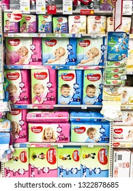 "Minsk, Belarus - February 15, 2019: Shelves with diapers under the brand ""Huggies"" of baby diapers for sale in supermarket. The trademark belongs to the company Kimberly-Clark Corporation since 1978"