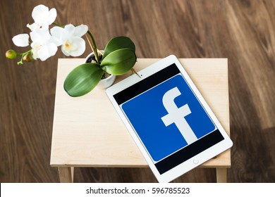 Minsk, Belarus - February 16, 2017: IPad Air Apple is on the table.  On the screen of the tablet is the logo of the well-known social network Facebook. Orchid flower.