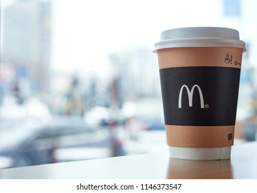 Minsk, Belarus, February 18, 2018: Paper cup of coffee with McDonald's logo on table near window on background of blurred city in McDonald's restaurant
