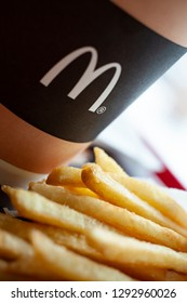 Minsk, Belarus, February 18, 2018: Paper cup of coffee with McDonald's logo close-up and French fries in McDonald's Restaurant