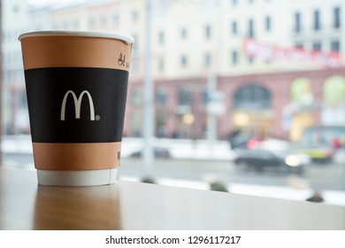 Minsk, Belarus, February 18, 2018: Paper cup of coffee with McDonald's logo on table near window on background of city in McDonald's restaurant