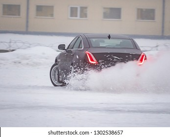 MINSK, BELARUS - FEBRUARY 2, 2019: All wheel drive Jaguar XJ skids and drifts on a slippery snow surface at the test-drive event in a winter driving school. Electronic Stability Program is off.