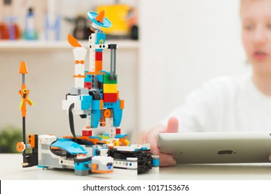 Minsk, Belarus. February, 2018. A teenager boy is programming a robot on IPad Apple. A robot assembled from a Lego Boost constructor. Classes on robotics. STEM education.
