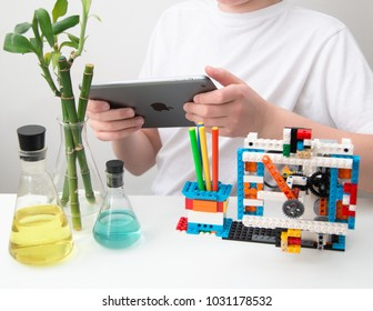 Minsk, Belarus. February, 2018.STEM education. Teenager boy code robot clock in the class of engineering and chemistry on laptop on Scratch. Lego Boost. Modern technologies.Robotics.