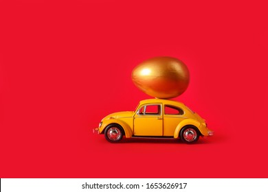 Minsk, Belarus - February 2020: Easter holiday. A yellow toy car carries a nest with gold eggs on a red background. Easter holiday card with retro car