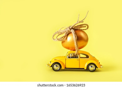 Minsk, Belarus - February 2020: Easter holiday. A yellow toy car carries a nest with colorful eggs on a yellow background. Easter holiday card with retro car